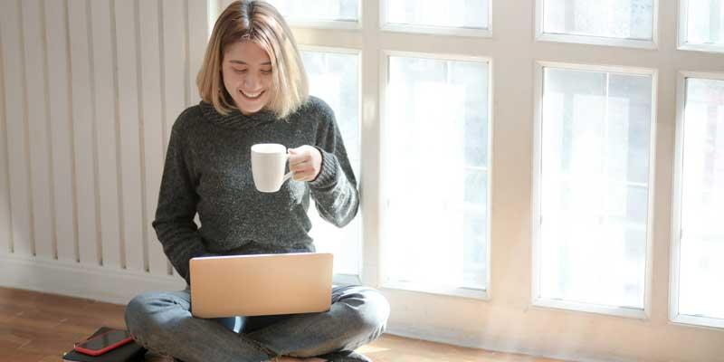 Women drinking coffee as she is on a laptop