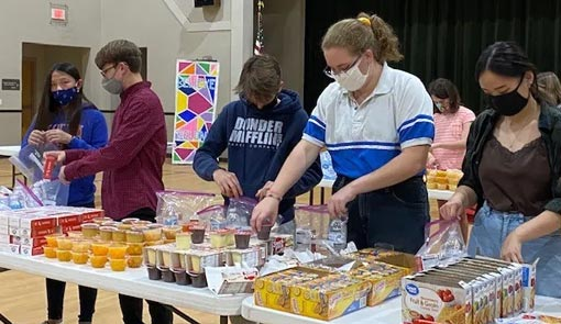 Youth putting food bags together